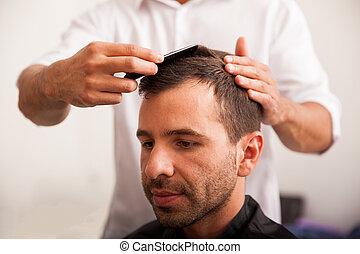 Hispanic man getting a haircut