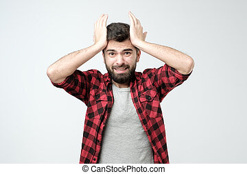 Young hispanic man is surprised with hand on head for mistake, remember error