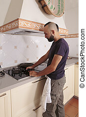 Young hispanic self-sufficient man lighting the stove - ...