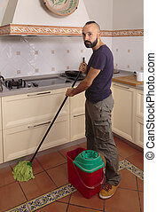 Young hispanic self-sufficient man mopping the floor - Young...