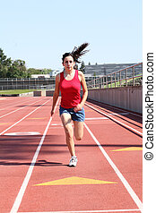 Young hispanic teen girl running on track