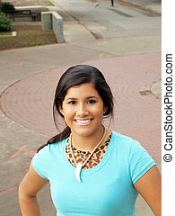 Young hispanic teen girl smiling outdoor portrait