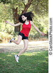 Young hispanic teen woman jumping outdoors