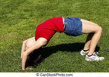 Young Hispanic Woman Bending Over Backwards On Green Grass