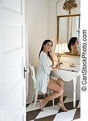 Young Hispanic woman putting on makeup