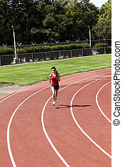 Young Hispanic Woman Running On Track Red Top Blue Shorts