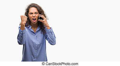 Young hispanic woman using smartphone annoyed and frustrated shouting with anger, crazy and yelling with raised hand, anger concept