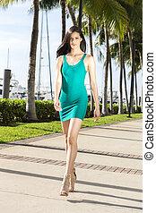 Young hispanic woman walking