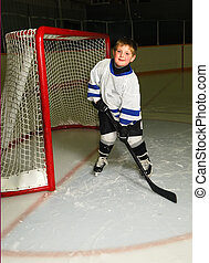 Young Hockey Player - A young boy in hockey pose in front of...