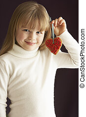 Young Holding Heart Shaped Cookie In Studio