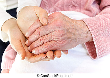 Young holding senior's hand