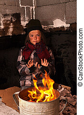 Young homeless boy on the street warming his hands at...