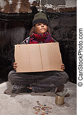Young homeless boy on the street with a sign