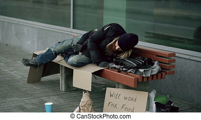 Young homeless drunk man preparing to sleep on cardboard on...