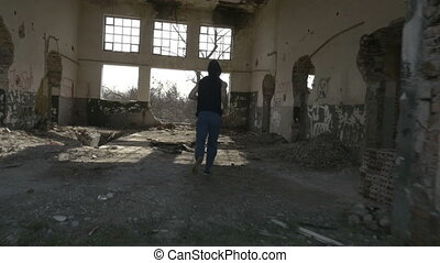 Young hooded man jogging in an abandoned building