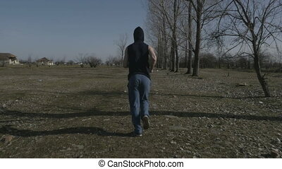 Young hooded man jogging in an abandoned place