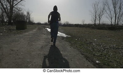 Young hooded man jogging in nature and jumping over a puddle