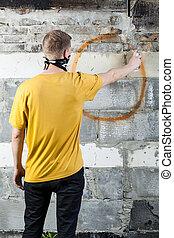 Young hooligan drawing a graffiti on the wall