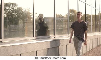 Young hooligan streetstyle guy in t-shirt going on the football stadium through a mirror windows at the evening at autumn