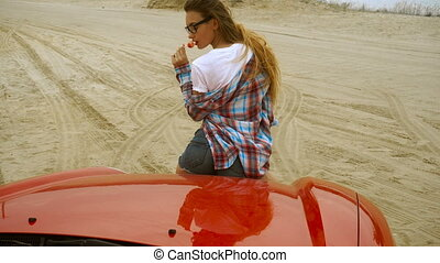young hot lady sits on a red car and licks a lollipop