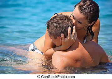 young hot woman sitting astride man in sea near coast, woman kisses man