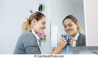 Young housewife cleaning and polishing mirror in bathroom