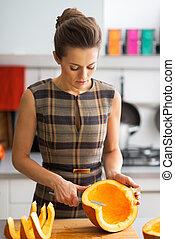 Young housewife cutting pumpkin in kitchen