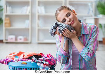 Young housewife doing laundry at home