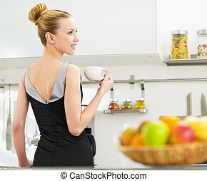 Young housewife drinking coffee in kitchen
