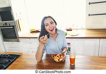 Young housewife eating fresh fruit salad