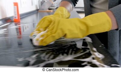 Young housewife in latex gloves washing electric hob on...