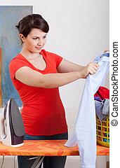 Young housewife ironing shirt