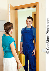 Young housewife  meeting happy repairman  at  home
