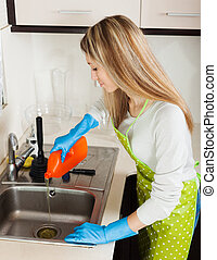 housewife pouring detergent into kitchen sink