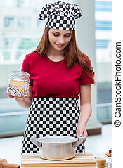 Young housewife preparing soup in kitchen
