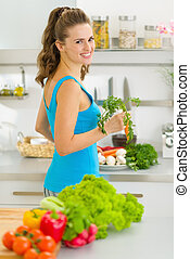 Young housewife preparing vegetables in kitchen