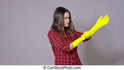 Young housewife putting on rubber gloves