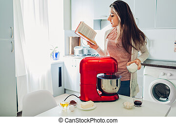 Young housewife reading recipe for cooking pie in culinary book. Woman using food processor on kitchen