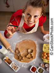 Young housewife showing Christmas cookie cutter while in kitchen