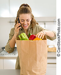 Young housewife sort purchases after shopping and talking ...