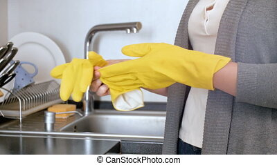 Young housewife taking off yellow latex gloves after doing...