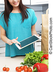 housewife uses a tablet computer in the kitchen