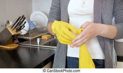 Young housewife wearing yellow latex gloves while doing...