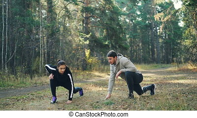 Young husband and wife are training in park together...
