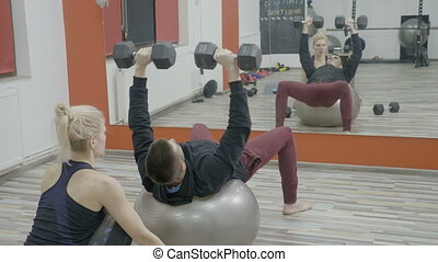 Young husband exercising on a pilates ball with dumbbells to...