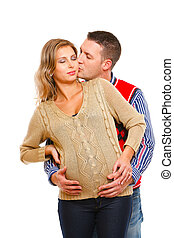 Young husband kissing his pregnant wife  on white background
