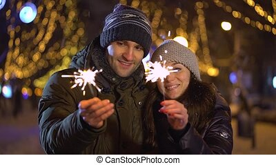 Young in love couple draws heart with sparklers in the air