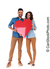 young in love couple holding big red heart