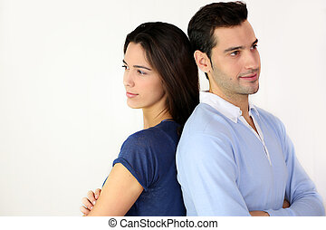 Young in love couple standing back to back