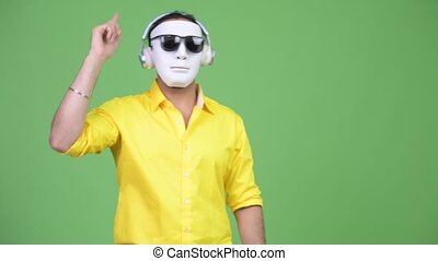 Young Indian businessman as DJ while wearing white mask